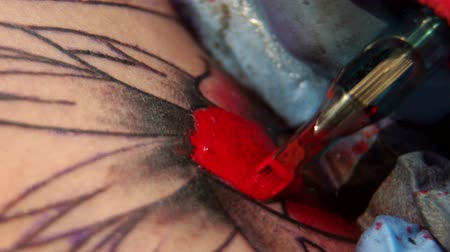 kár : Close-up of a tattoo artist doing a tattoo on a mans arm, he fills with a red ink outline of a tattoo. Slow motion. Close-up of a tattoo machine with red ink.