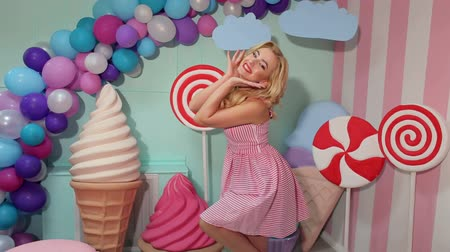 pinup : Portrait of a cheerful dancing girl in a pink striped dress and hairstyle on the background of the interior with big sweets- candy, marshmallows, ice cream and balloons.