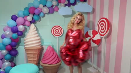 леденец : A happy girl in a pink dress is holding a lot of red balloons and is spinning around herself in the studio with a sweet interior.