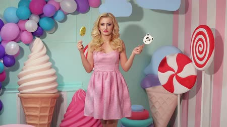 infantil : A young girl in bright clothes with lollipops in her hands in a studio with balloons, marshmallows and ice cream. Barbie style. Candy girl.