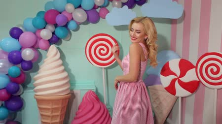pinup : A glamorous fashion girl in a pink dress poses in the studio against a background of colorful balls and huge lollipops and marshmallows. Barbie girl.