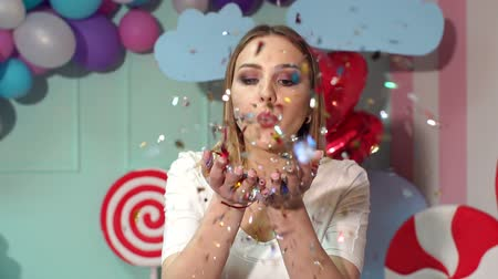 cicili bicili : A happy girl with blond hair in a pink dress blows on a tinsel or confetti in a room with huge sweets, ice cream, marshmallows and lollipops. Slow motion. Stok Video