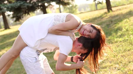 jumped : Beautiful charming young girl jumped on back to her handsome boyfriend, they are fun circling in the park at sunset. Slow motion. Girl in a white dress jumped fun on the guys back, they are laughing. Stock Footage