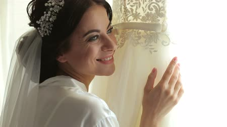 véu : Bride in silk dressing gown holding and admiring her beautiful wedding dress in front of the window. Wedding morning, brides preparations. Gorgeous bride in luxury dress is getting ready for wedding.