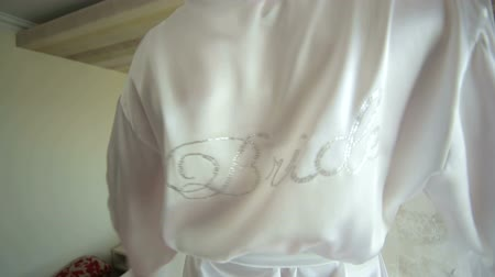 negligee : Happy bride in a silk negligee with the inscription Bride dancing back to the camera. Happy morning of the bride. Stock Footage