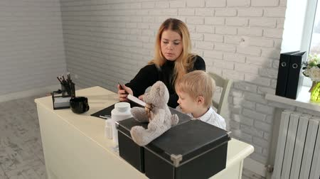 плюшевый мишка : Mom and son are sitting at the Desk and reading a book. A caring mother reads a book to her son. Стоковые видеозаписи