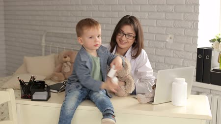 paediatrician : A young woman doctor playing with a little boy in a childrens clinic in the office, the baby holds a white bottle of medicine. Portrait of a little boy in the doctors office. Stock Footage