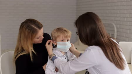 poznámkový blok : Close-up of a little boy in a medical mask at a reception at the pediatrician. The doctor puts a protective mask on the little boy who sits in the arms of his mother in a childrens hospital.