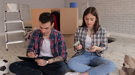 ипотека : A young couple counting money and writing down their expenses in a notepad sitting on the floor in their new apartment. Housewarming.