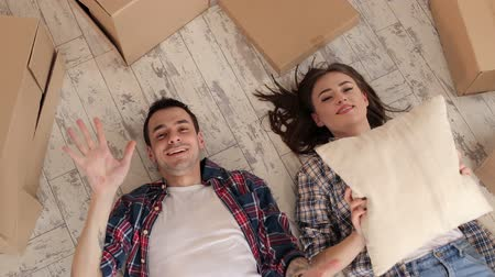 relacje : A happy couple lies on the floor among the unmade boxes in the new apartment and throw up the pillows. Young couple moving in a new home. Wideo