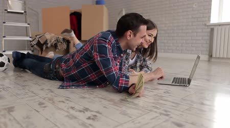 belongings : A happy couple in plaid shirts lay on the floor in a new apartment with a laptop. Young couple with laptop on the floor in a new house. Portrait. Stock Footage