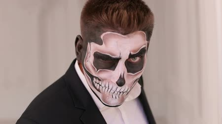 reojo : Close-up portrait of a man with a skull makeup dressed in a tail-coat. Dia de los muertos. Day of The Dead. Halloween. Portrait of man in suit with Halloween skull make-up showing his emotions.