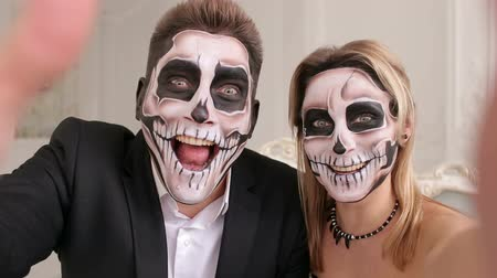 very : Portrait of scary people with a terrible makeup in the form of a skull or dead people. Couple very scared laughing showing teeth. Outfit for halloween. A couple of zombies take selfies on Halloween.