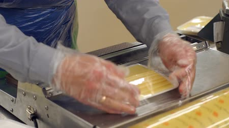cheese slice : Close-up of a saleswoman slicing cheese in a supermarket and wrapping it in cling film. Packaging of chopped cheese in a supermarket worker. Stock Footage