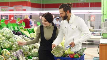 karnabahar : Beautiful young smiling couple choosing cauliflower in supermarket together. Beautiful young couple choosing products in supermarket and looking at each other with smile. Vegetarianism. Stok Video