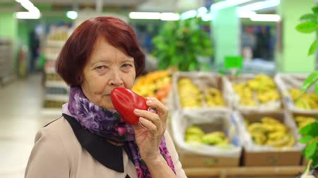nákupní vozík : Good-looking senior woman holding red pepper, examining it with care, smiling while grocery shopping in supermarket, standing in front of boxes filled with fresh fruits and vegetables.