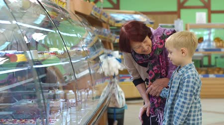 słodycze : An old grandmother with a small grandson in the supermarket choose sweets on the counter. Portrait of an elderly woman with a child in the supermarket. A grandmother with a grandson to buy a cake.