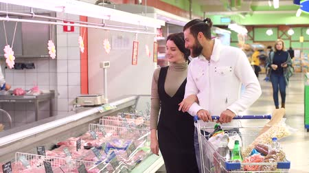 vetrina : Food, sale, consumerism and people concept - happy couple with shopping cart buying meat at grocery store or supermarket. Positive smiling family couple choosing chilled meat in food store.