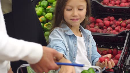 selecionando : Close-up of a little girl puts in a grocery basket fresh radish, a girl buys vegetables with their parents in the supermarket. Portrait. Slow motion. Family at the grocery store.