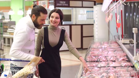 tavuk : Happy young people buy fresh meat in a large supermarket, they carefully look at the shop window and choose high-quality meat. Shopping, food, sale, consumerism and people concept