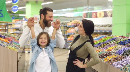 supermarket food : Portrait of a young family in a pastry shop, dad holds his daughters hands and lifts her. Happy family shopping in a large supermarket, they talk, laugh and have fun.
