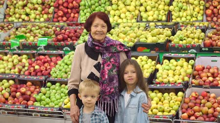 представитель старшего поколения : Happy cheerful elderly woman in her grandchildren to buy food and fruit at the supermarket. Portrait of grandmother and grandchildren on the background of boxes of apples in the grocery store.