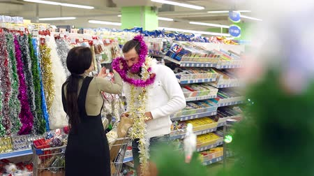 festoon : Happy loving couple buying Christmas decorations and gifts for Christmas. The girl puts a garland on her boyfriends head, the couple is having fun at the Christmas holidays in the supermarket.Slow mo