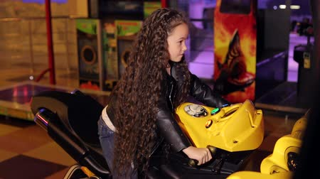 oturur : A little girl with long curly hair plays video games in a modern childrens room, she sits on a motorcycle and pretends to be riding. Modern shopping mall playground for kids and video games.