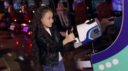 hajtások : A little girl with long curly hair plays video games in a modern childrens room. Modern shopping mall playground for kids and video games. Stock mozgókép