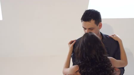чувственный : Young people dance in a dance school for Latin music. Salsa, bachata, rumba. Beautiful couple dancing bachata on white background in studio. Стоковые видеозаписи