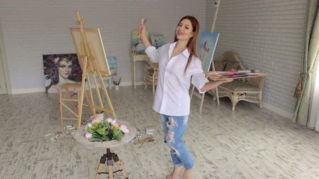 ustalık : A happy creative girl artist in a white shirt and jeans spinning around herself in a studio among many paintings. Young artist painting in the house. Art.