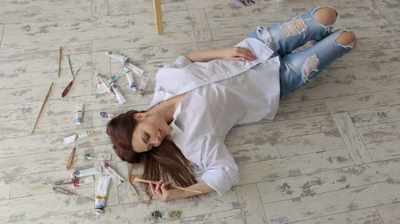 spousta : Sexy girl artist lies on the floor among the many different tubes of paint in the drawing Studio.