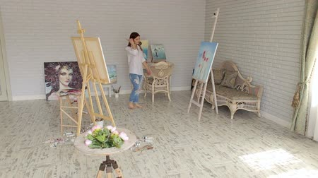 ustalık : A young girl artist in a white mens shirt and ripped jeans walks through the drawing Studio among paintings and canvases. Portrait of a talented girl artist in the Studio.