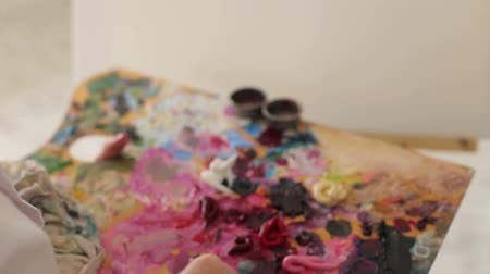 oilpaint : The artist mixes oil paints on a palette with a brush, close-up. The artist works in a drawing Studio.