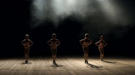 театр : Four little girls in beige swimwear, pantyhose and ballet dancing on stage on a black background, slow motion.