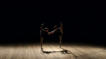 sznurek : Two flexible young teen girls show gymnastic exercises on stage on a black background. Two girls stand in a vertical gymnastic twine on stage in the dark. Silhouette of two ballerinas on stage.