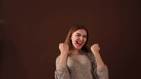 raises : Portrait of a successful woman in the Studio on a brown background, she screams and raises his hands up. Slow motion.