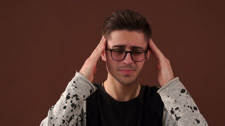 discomfort : Handsome young man in glasses touching his head with hand feeling strong headache against the brown wall.