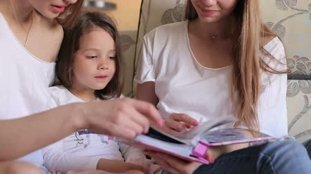 разорвал : Close-up of mom and daughter and sister watching the photo album at home on the couch. Three sisters of different ages are watching an album with photos of the house on the couch.