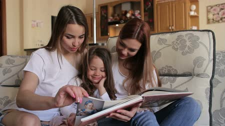 yaşlılar : Three sister, two adults and one a small, look photo album sitting on couch. A young mother with a small daughter and an older sister watching a photo album at home on the couch.