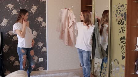 tentar : Two twin sisters measure the same jackets in front of the mirror in the bedroom. Choice of clothes. Two girls measure clothes in front of a mirror.
