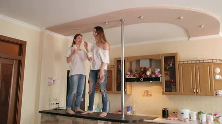 together trust : Two cheerful girls with champagne in their hands dance and sing in the kitchen on the bar. Two sexy girls dance at home in the kitchen on the bar or on the table. Stock Footage