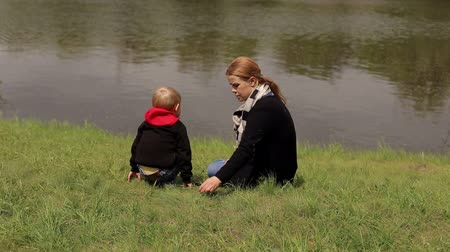 sentarse : A young woman with long blond hair in a black cardigan sits on the shore of a small lake with her son. Mom and child are walking in the park near a small pond, they sat down on the grass to rest