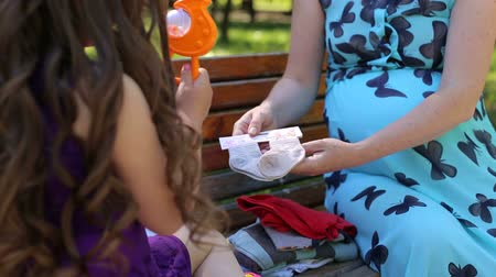 ubrania : A pregnant woman sits with her daughter on a park bench in the summer and looks at clothes for a future baby.