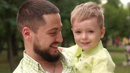 omzunda : Portrait of a happy bearded man with his son in the Park in the summer. Father and son play in the summer Park in warm Sunny weather. Close-up. Slow motion.