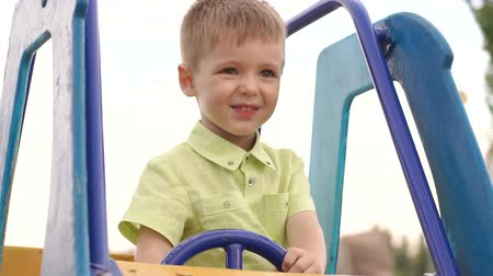 speelgoed auto : The child is sitting at the wheel of a childrens car in the playground. A little boy sitting on the car on the Playground in the summer in the Park.