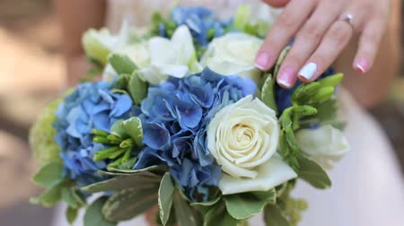 canteiro de flores : Close-up of the bride holding her wedding bouquet, she gently touches the flowers.