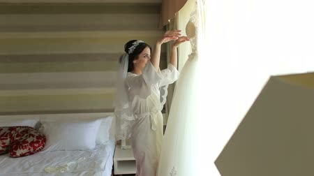 невеста : Bride in silk dressing gown holding and admiring her beautiful wedding dress in front of the window. Wedding morning, brides preparations. Gorgeous bride in luxury dress is getting ready for wedding.