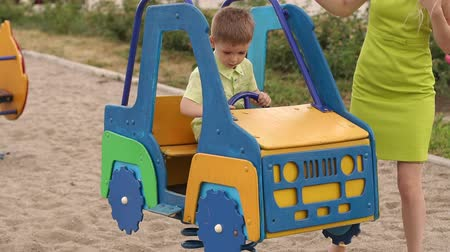 nevinný : A little cute boy playing on the Playground in a toy car, his mother is standing next. Slow motion.