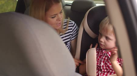 caring : Close-up of a little boy sitting in a car seat in the back seat of a car, his mother is sitting next to him and they are talking. Slow motion. Stock Footage